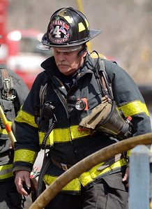 Fitchburg FF Randy Doughty works at a brush fire extended to a house on 4th Ave in Leominster.