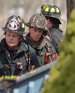 Fitchburg FFs Lieut Mike Gelionas (middle) and Randy Doughty (l) work at a brush fire extended to a house on 4th Ave in Leominster.