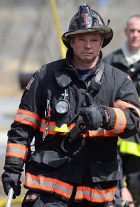 Leominster Fire Lieut Craig Long works at a brush fire extended to a house on 4th Ave in Leominster.