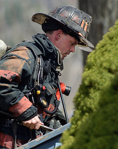 Fitchburg Fire Lieut Mike Gelinas works at a brush fire extended to a house on 4th Ave in Leominster.