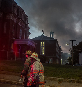 Fitchburg Chief Kevin Roy (left) and Deputy Chief Tad Dateo walk past the former Annex with smoke drifting past the Academy St School during the 4th Alm fire at the former BF Brown School.