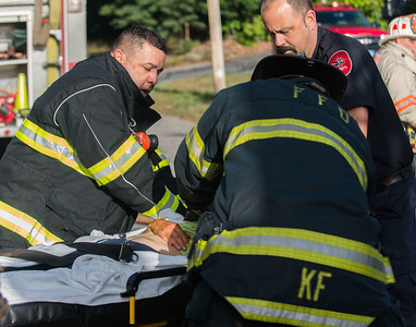 Fitchburg firefighters and MedStar EMS work on a victim rescued from a house fire on Cottage St.