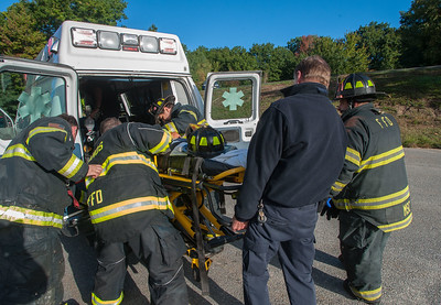 Fitchburg firefighters and MedStar EMS rush a victim of a Cottage St house fire into a waiting ambulance.