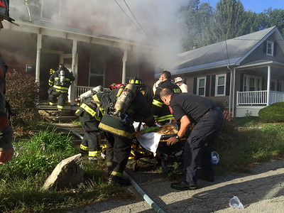 Firefighters and MedStar EMS rush a victim of a Cottage St house fire to a waiting ambulance.