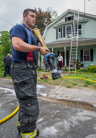 Fitchburg firefighter John Girouard picks up a length of hose after a basement fire at 87 Roosevelt St in Fitchburg.