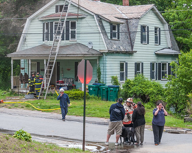 Fitchburg Deputy Fire Chief Dave Gravel (bottom right-white coat) talks with the home ower after a fire at 87 Roosevelt St.