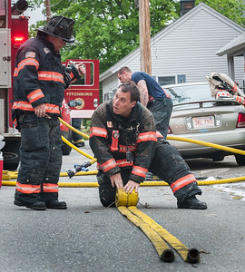 Fitchburg Fire Lt Patrick Roy (R) confers with Lt Jack Gilmartin while rolling up a length of hose after a basement fire at 87 Roosevelt St in Fitchburg.