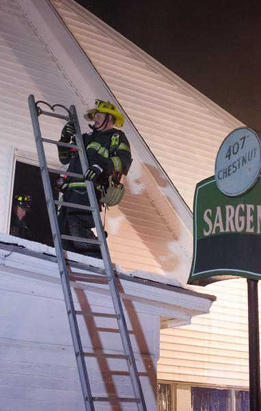 Gardner Fire Lieut Craig Osowski climbs a ground ladder into an exposure during a 4th Alm at 403 Chestnut St.