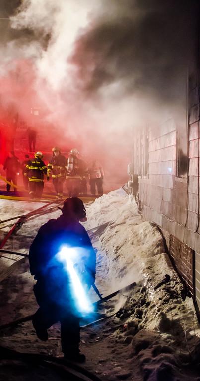 A FF's LED flashlight cuts through the smoke at a 4th Alm fire 403 Chestnut St Gardner.