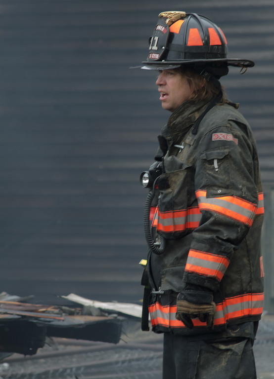Gardner FF Andy Fields looks over the scene after a 6 Alm fire on Sherman St.