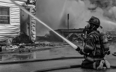 A Gardner FF plays a hand line into the fully involved vacant apartment building on Sherman St during the 6 Alm fire.