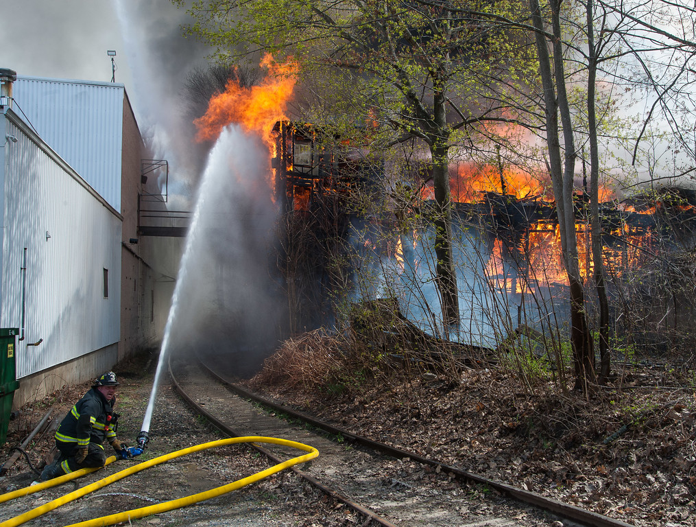 Gardner firefighter Eric Hulette puts a deck gun in action at the rear of a fully involved vacant factory on Sherman St. New England Woodenware on Logan St was damaged, but ultimately saved.