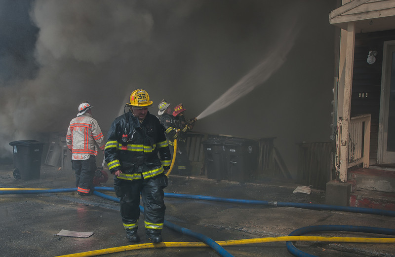 Westminster Captain Kyle Butterfield walks away from crews protecting an exposure next to a fully involved vacant factory on Sherman St in Gardner.