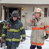 Smoke could be seen at 21 Normal Road in Fitchburg on Tuesday. Firefighter work to put out out the fire. Deputy Fire Chief David Rousseau radios in the current situation at the scene. SENTINEL & ENTERPRISE/JOHN LOVE