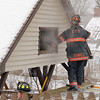 Smoke could be seen at 21 Normal Road in Fitchburg on Tuesday. Firefighter Edward Suarez looks for hotspots in the roof of an over hang at the home. SENTINEL & ENTERPRISE/JOHN LOVE