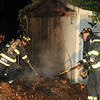 Firefighters pull the debris away from the shed so it can be extinguished<br /> <br /> Photo Scott LaPrade