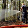 A brush fire broke out at the Notown Reservoir in Leominster on Wednesday afternoon. Leominster Firefighter Jeff Vaillette sprays down some hots spots on the fire. SENTINEL & ENTERPRISE/JOHN LOVE