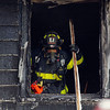 Flames can be seen at the base of the house at 301 Pratt Street in Fitchburg on Friday afternoon were a fie broke out. A Leominster firefighter can be seen in the window of the house working the fire as the fire winds down. SENTINEL & ENTERPRISE/JOHN LOVE