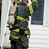 A fire broke out at 301 Pratt Street in Fitchburg on Friday afternoon. A firefighter stays cool by dumping water on his head after fighting the fire. SENTINEL & ENTERPRISE/JOHN LOVE