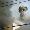 Flames can be seen at the base of the house at 301 Pratt Street in Fitchburg on Friday afternoon were a fie broke out. A Fitchburg firefighter was surrounded in smoke as he cuts into the roof during the fire. SENTINEL & ENTERPRISE/JOHN LOVE