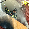 Firefighter Robert Penning opens up the area of fire<br /> <br /> Photo Scott LaPrade