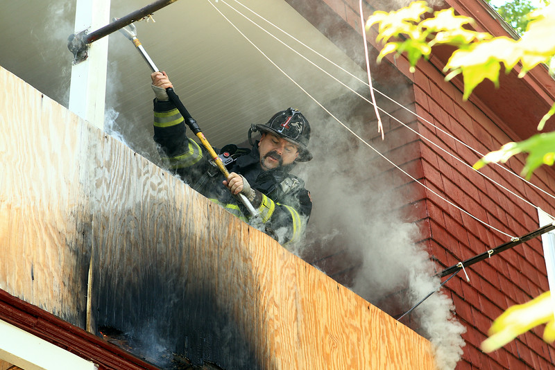 Firefighter Robert Penning opens up the area of fire<br /> <br /> Photo Scott LaPrade