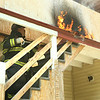 Firefighter Robert Penning gets up to the area of the fire on the porch<br /> <br /> Photo Scott LaPrade