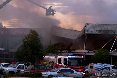 Fire continues to burn under the collapsed roof