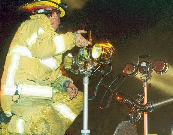 A firefighter adjusting the lighting at a Burbank Fire
