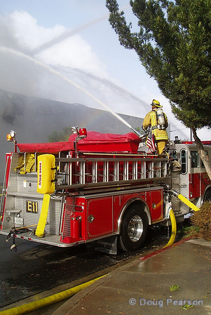 A Burbank Firefighter operates a deck gun on a building that had exploded.