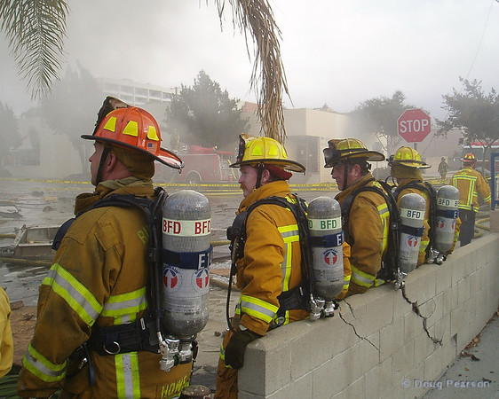 Firefighters standby after an explosion and fire at a concrete block building in Burbank.