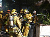Firefighters check the nozzle before going in to the fire.