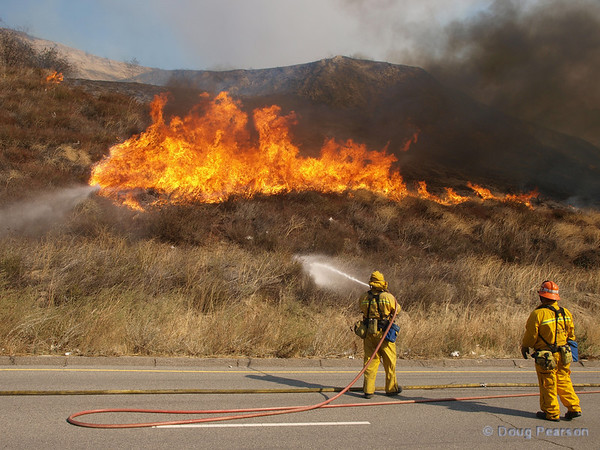 Firefighters wet down the grass ahead of the fire in order to control the spread of the fire.