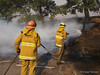 Crew from LA City Fire Department Engine 39 extinguish a spot fire along the freeway during the Sayre Fire.