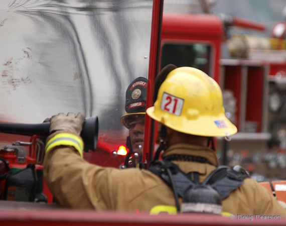 Truck 21 engineer from Glendale City Fire Department putting away equipment after a fire in Los Angeles.