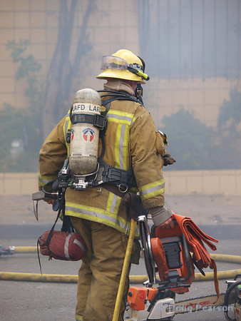 LA City Fire Department firefighter picking up equipment after a fire.