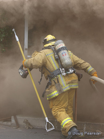 LAFD Firefighter pulling a line to assist an interior attack.