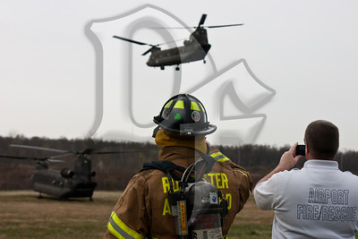 A firefighter from Greater Rochester International Airport Fire Department watches along with the Rochester Airport Fire Chief as two CH-47 Chinooks from the NY Army National Guard prepare to depart a landing zone in Chili, NY. The helicopters were picking up US Marines of the Anti-Terrorism Battalion, A Company, who were going to Fort Drum near Watertown, NY for their drill weekend.