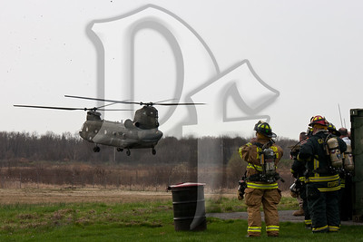 Firefighters from the Greater Rochester International Airport Fire Department and Gates Fire District watch a CH-47 Chinook land behind the US Marine Corps Reserve Center in Chili, NY. The firefighters provided a standby for the Army National Guard helicopters, which are based at the Rochester Airport, while they picked up Marines of the Anti-Terrorism  Battalion, A Co., for their drill weekend at Fort Drum near Watertown, NY.