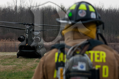 A firefighter from Greater Rochester International Airport Fire Department watches as a CH-47 Chinook from the NY Army National Guard prepares to depart a landing zone in Chili, NY. The helicopter was picking up US Marines of the Anti-Terrorism Battalion, A Company, who were going to Fort Drum near Watertown, NY for their drill weekend.