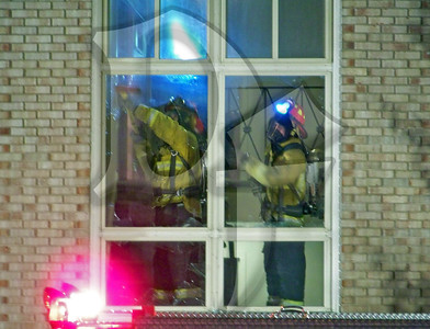 Firefighters work on clearing a window in the stairwell for ventilation.