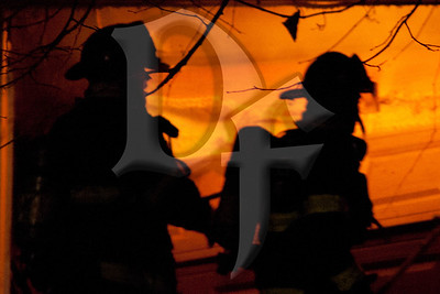 Firefighters silhouetted by fire in the garage of a home on Varian Ln. in Gates, NY. This was the second of two fatal fires reported within an hour in the town. January 20, 2012.