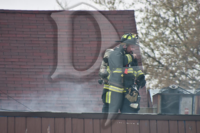 A Gates firefighter relays the conditions on the roof of a building that suffered damage from a vehicle fire against the side wall.
