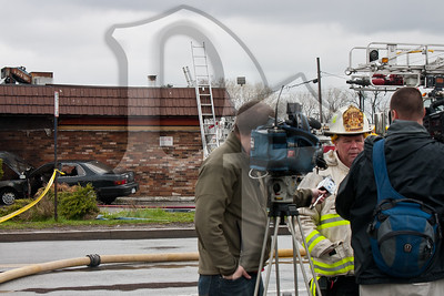 Chief Jim Harrington of the Gates Fire District briefs the media after firefighters from Gates and RIdge Road extinguished a vehicle fire against the side of a former gas station.