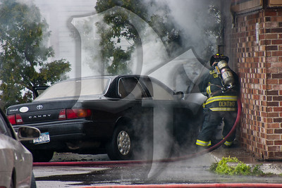 A Gates, NY Firefighter works to control a vehicle fire and keep it from spreading to a vacant building.