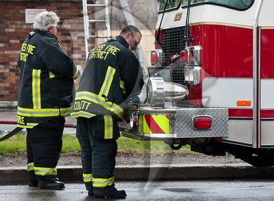 Gates firefighters repack the hose on the front of Quint 4530 after extinguishing a vehicle fire against the side of a building.