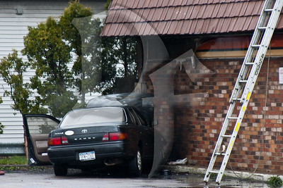 A vehicle rests near the side of a former gas station after firefighters from the Gates and Ridge Road Fire Districts extinguished a fire that nearly spread to the vacant building.