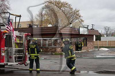 Gates firefighters return an extension ladder to Quint 4530 at the scene of a working fire.