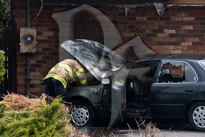 A Fire Investigator from the Monroe County Fire Bureau begins his investigation into the cause of a vehicle fire that nearly spread into an adjacent building.