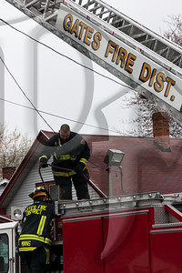 Gates, NY firefighters reload hose onto the cross-lays of Quint 4530 after extinguishing a fire.